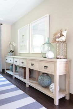 Framed photos of beach scenes set the tone for this coastal-inspired dining room. A long, weathered wood buffet table showcases beachy vignettes with sculptural coral and nautical jars.