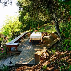 A deck with a view is the new destination near the top of the slope. Benches and a retaining wall wrap around the deck.