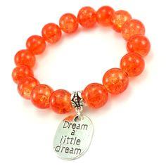 Bransoletka wykonana ręcznie zkoralików szklanych pomarańczowych kulek i dodatków w kolorze srebrnym. Dodatkowozawieszka charmsz napisem dream a little dream.