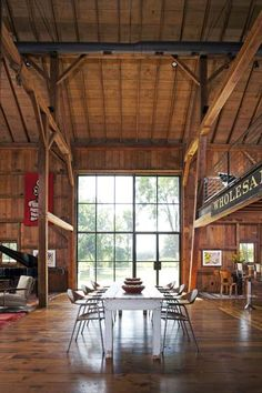The original post-and-beam frame is lined with reclaimed barn wood and has a dining area illuminated by soaring steel-framed glass panels. The master suite sits hayloft-style over the kitchen. | Photo: James Yochum