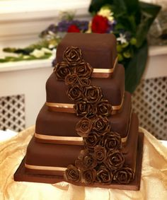 Chocolate wedding cake with gold ribbon and cascading chocolate gum paste roses.  ᘡղbᘠ