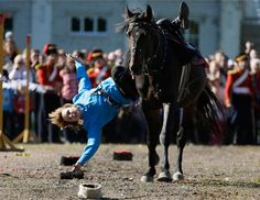 A female member of a Russian traditional riding club picks up a hat during a festival in St. Petersburg marking the 200th anniversary of the battle of Borodino, which in 1812 was the largest and bloodiest single-day action of the French invasion of Russia.