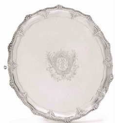 AN IMPORTANT AMERICAN SILVER SALVER, RICHARD HUMPHREYS, PHILADELPHIA, CIRCA 1775 – On four high claw & ball feet with foliate headers fluted & gadroon rim with foliated cartouches at the points, the caveto with chased leaves at the angles, large floral cartouche in center of tray surrounding elaborate engraved script initials GE, marked R. Humphreys in script in a shaped cartouche on bottom 3 times. 47Oz, diameter 16 ½ in.