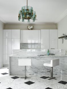 Marble tiles in this modern kitchen of London designer Colin Radcliffe's Notting Hill townhouse set the foundation for a cool, clean space. The design is markedly modern, with the exception of a 1950s FontanaArte chandelier and 1970s barstools. The cabinetry is custom made, and the refrigerators are by Liebherr.