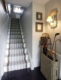 Lovely stair carpet (could be painted too) combined with rustic basket with a cornucopia of contents and simple traditional wall light and pictures.