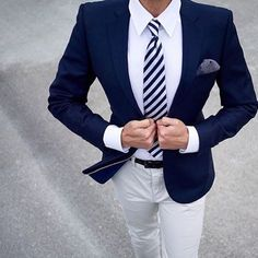 A navy blazer and beige casual trousers are a great outfit formula to have in your arsenal. Shop this look on Lookastic: https://lookastic.com/men/looks/blazer-dress-shirt-chinos/24056 — White Dress Shirt — Navy and White Vertical Striped Tie — Navy and White Polka Dot Pocket Square — Navy Blazer — Black Leather Belt — Beige Chinos