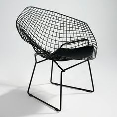 a lovely pair of bertoia diamond chairs on top of a nelson bench