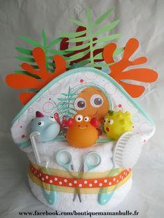 Gâteau de couches Nemo - thème bain est composé de : -21 couches taille 3, de 4 à 9kg -1 cape de bain Nemo -1 ensemble peigne et brosse -1 paire ciseaux à bouts ron - 5644753