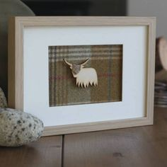 Highland Cow on Tartan raised and framed in a lovely oak coloured rectangular frame.Our Highland Cow on tartan is designed, handmade and professionally framed in the UK. This unique handmade piece of artwork is beautiful in its composition. A highland cow cut out fixed to a bed of tartan with a little piece of tartan detail to the head of the cow. Finished with a white mount and professionally framed in an oak coloured surround. Other styles and designs are available.material and wood23 x…