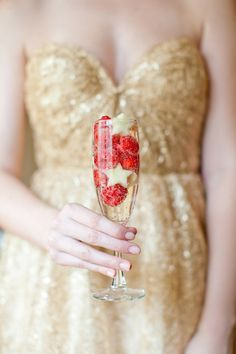 Add raspberries and apples to a glass of holiday champagne.