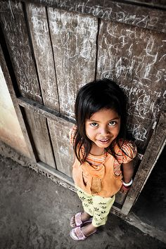 A portrait of cheerful Vietnamese girl in the Central Highlands region of Vietnam, standing outside the door of her home.