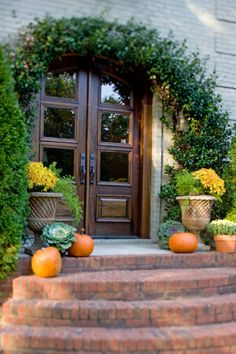Love the arching greenery over the glass panel doors with a wide brick staircase.  Don't you just love how the orange pumpkins, kale and planters of mum, pop?
