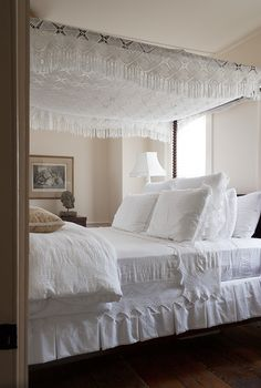 A bedroom favors texture over color, with a white-on-white bed and rug in Smith's preferred washed-out hues.