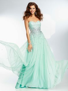 Paparazzi mint prom dress 95090 (2014) has a fitted bodice, which is adorned with sparkly jewels, and a heavily beaded empire waist. Completing this chiffon Paparazzi prom dress is a flowing floor length skirt with scattered beading. The cute and affordable Paparazzi prom dress is available in mint and coral, two of the hottest colors for this season ~ Young Brunette Woman Wearing a Mint Green Formal Evening Dress w. Beaded Bodice.. Features: ...