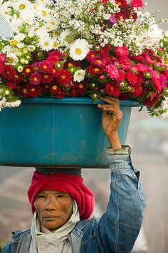 Mon woman with basket of flowers on her head in Sangklaburi, Thailand