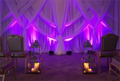 White ornate swagged backdrop with large and medium coach lanterns, pillar candle clusters, and LED uplighters in purple by www.stressfreehire.com #venuetransformers
