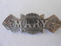 A silver name pin, Mary, with the makers mark TA.  The ivy leaves on either side mean friendship in the language of flowers.