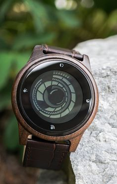 A wood watch with a touch screen display. A spiralling time display framed beneath a sleek concave lens, Kisai Vortex Wood is a limited edition touch-screen watch with a host of features. Two time zones, seconds, date, alarm, animation, LED light-up, audio feedback and touch screen operation, all housed in a natural dark sandalwood case with genuine leather strap. #uniquewatches #woodwatches #watchdesign #coolwatches #japanesewatches