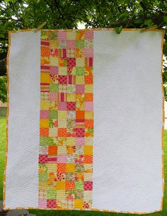 Summer Citrus Baby Quilt by teaginny, via Flickr - I love the use of small colorful squares with the solid