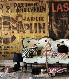 An industrial space, mixed with eclectic wonders meets vintage in this charming living space . Wonderful old hand-painted entertainment advertisements on linen hang as works of art creating the perfect backdrop for this living room. | Caption by Jenn Brown