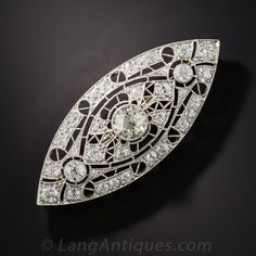 1.75 Carat Center Diamond and Platinum Art Deco Brooch. Measuring over 2 inches long, this stunning and impressive Art Deco brooch, circa 1920s, sparkles dead center with a gorgeous, collet-set European-cut diamond, weighing 1.75 carats. The elegantly designed navette shape brooch is rendered in platinum and ornamented with a geometric lace work background aglitter with just under 3 carats of smaller, deep European-cut diamonds - bringing the total diamond weight to 4.60 carats.