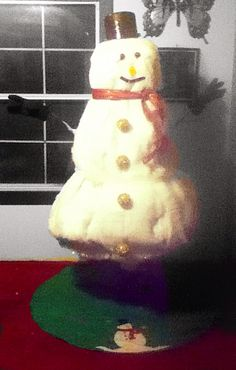 Christmas tree snowman. Used blanket snow (body), ribbon (scarf), metal pot (hat), measuring spoons (eyes), pop lid (nose), electrical tape (mouth), fluffy ornaments (buttons), white garland (body dividers), and real twigs and gloves.