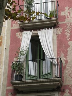 Sweet balcony and french doors. Don't think I've ever seen curtains on the outside of the windows before.