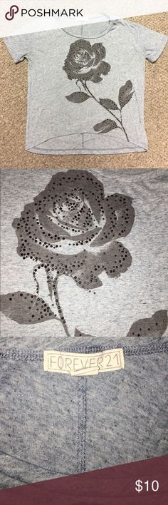 Forever 21 embellished rose top! Worn once! Forever 21 embellished rose top! The top has a loose fit, and is also slightly a high/low. The top has a faded denim color to it, and can seen best in the picture with the Forever 21 tag. (Even though the pictures look gray) It was worn only once, so it is practically new! Forever 21 Tops Tees - Short Sleeve