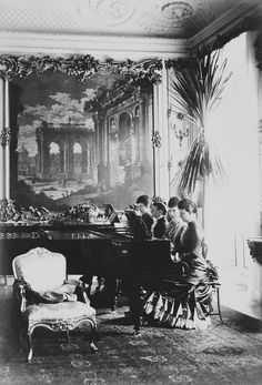 Queen Louise of Denmark with her three daughters at the piano. From left to right are Alexandra, Princess of Wales (1844 -1925); Empress Mararie Feodorovna of Russia (1847-1928) facing the viewer, Queen Louise of Denmark and Thyra, Duchess of Cumberland (1853-1933)