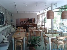 cafe feel for kitchen; two-toned cream and natural kitchen table/chairs with bench; brick, wicker and natural elements