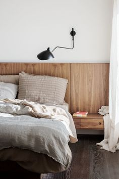 Bedroom Ideas - This modern ebdroom includes a custom designed wood headboard that includes built-in side tables.