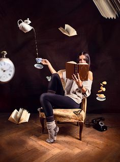 Young girl reading a book in a surreal situation with objects flying
