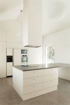 cocina blanca minimalista con isla central para zona de cocción y barra