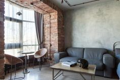 I love the sitting area in the bay window. Cute chairs.  Exposed brick apartment.