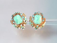 Marked Czechoslovakia. Ornate gold over brass with enamel detail. Screw-back earrings with czech glass cabs and aqua blue rhinestones.