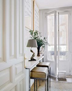 lightfilled + lovely woodwork wall, fantastic black and white art Camel accent and iron lamp details