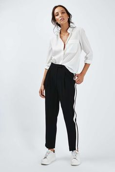 black trousers with white side stripes | white button-up | white sneakers