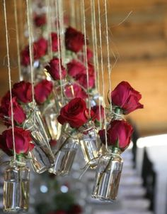 Love these hanging jar vases that use wild flowers instead of roses for a outdoor rustic feel