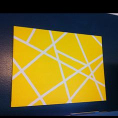 Yellow and white masking tape canvas on navy wall