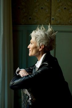 coupe cheveux courts, couleur cendres, avec des crêtes formées avec du gel sur le haut, style de coiffure rock et punk, femme âgée dans un décor baroque