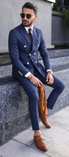 Dapper combo inspiration with a navy pinstripe double breasted suit white button up shirt brown tie sunglasses wrist accessories brown leather banded watch no show socks brown single monk shoes. Mens Blue Pinstripe Suit, Double Breasted Pinstripe Suit, Mens Tweed Suit, Black Suit Men, Mens Fashion Suits, Mens Suits, Men's Fashion, Tweed Wedding Suits, Suit Guide