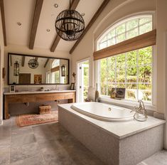 In the airy master bath of Wendy Bellissimo's California dream house, exposed wood beams hover over a large soaking tub.