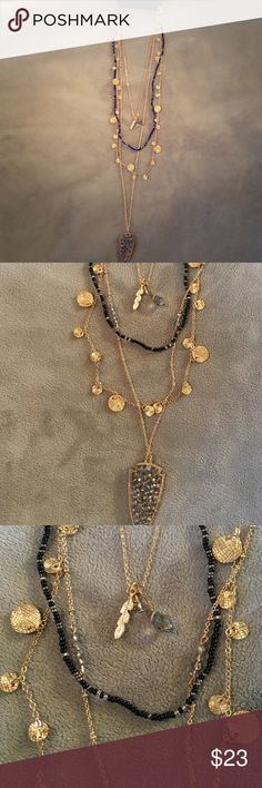 Express Necklace 4 in 1 neck lace. Has three gold chains and  a black beaded one. Two sets of charms. Express Jewelry Necklaces