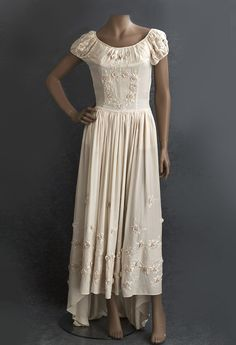 Embroidered silk wedding dress, 1930s Elaborately embroidered with three-dimensional roses of matching silk floss, our ivory silk crepe dress showcases a masterful floral design, where art has exhausted all its invention.  The low-waisted bodice is form fitting below the neckline. The full skirt dips to a graceful train in back. The dress closes on the side with snaps.  The shirred, low-scoop neckline and gently puffed sleeves are of the last degree of feminine charm.