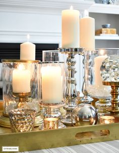 Make a visual statement with a clustered grouping of metal and glass candleholders in varying heights on your coffee table. Coffee Table Styling, Decorating Coffee Tables, Light Wooden Floor, White Decor, Decorating Tips, Holiday Decorating, Pillar Candles, Candle Holders, Table Decorations