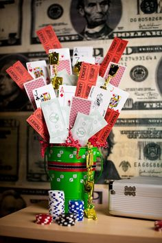 Centerpieces made out of play money, playing cards, and raffle tickets attached to skewers. Put them all into a buckets and add some dice stickers, coordinating ribbon and some poker chips, and you have a nice little casino display.