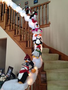 Penguin snow slide! I put garland down first, then lights, then fluffy snow. The garland helps attach the snow. I sewed a piece of thread through the back of each penguin and then around the banister to hold them upright.
