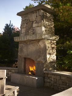 The Knickerbocker Group Grotto fireplace has unique masonry, with three large, rough-cut stones framing the fire above a massive hand-split hearth, is highlighted against the dark evergreen foliage.
