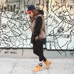 """""""Timbs are my go-to for fall and winter. I'm quite certain they go with anything and everything, and you will see me in these a lot. A big hoodie under a faux fur vest, covering second-day hair with a fitted cap does it for me. The Nike Leg-A-See leggings are a nice change from basic black tights."""" - Anna"""