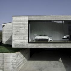 The four concrete wings of this house in Girona, Spain, appear to hover in the air above an underground entrance